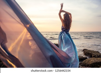 Beautiful brunette girl in blue gray chameleon dress with long train sitting on a beach at amazing sunset. woman in chic outfit near a rock on a tropical paradise island enjoying solitude and freedom