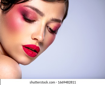 Beautiful brunette girl with bright eye makeup. Beautiful fashion woman with  a red lipstick on her lips. Glamour fashion model with vivid make-up. Stylish fashionable concept. Art. Beauty  face.