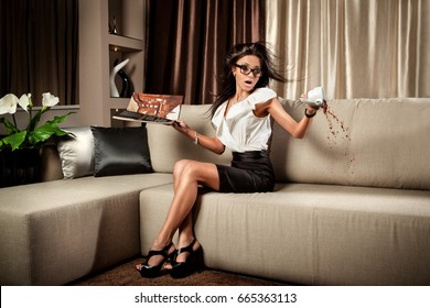 Beautiful brunette girl in business clothes spilling coffee from a cup on a sofa