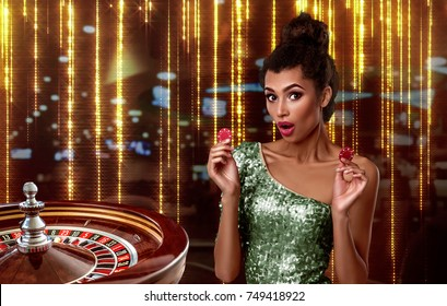 beautiful brunette girl with chips stands on the background of a royal roulette. collage with a gambler, roulette and chips