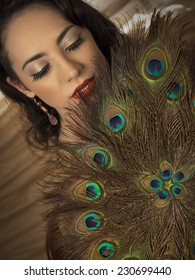 Beautiful brunette girl close up with closed eyes and hand fan made of peacock feather