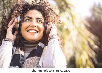 Beautiful brunette girl with curly hair listening to music with her headphones, enjoying the good vibes of the sound - Portrait of a pretty woman standing in a park on a sunny day relaxing with music
