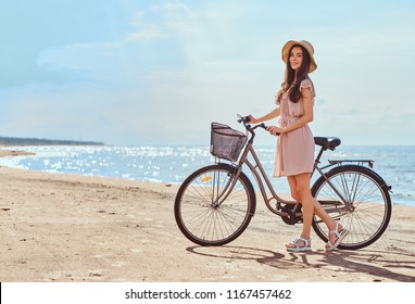 Beautiful brunette girl dressed in dress and hat posing with a bicycle on the beach on a sunny day.