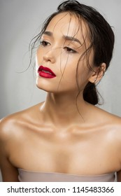 Beautiful brunette girl fashion model with naked shoulders and wet hair on a gray background. Nude make-up, red lips. Healthy clean skin. Advertising and commercial design.