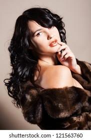 Beautiful brunette girl in fur coat in studio