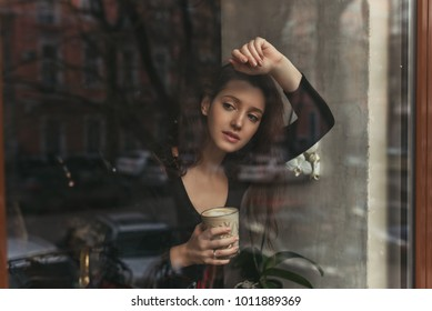 beautiful brunette girl with a glass of coffee behind the glass, portrait, coffee shop window, concept of female emotions