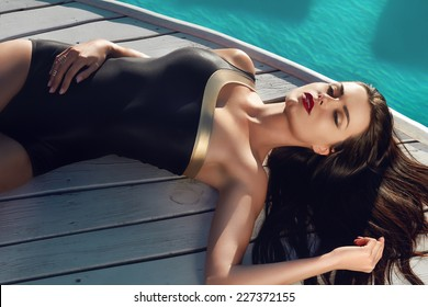 Beautiful brunette girl in good shape with long dark hair and tan skin red lips in black swimming suite with golden line with modern rings lie near the pool with green water closing her eyes and smile