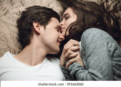 beautiful brunette girl and guy lying in bed and holding tightly hands. The concept of tenderness and affection
