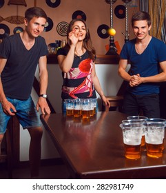 Beautiful brunette girl having fun with twins playing beer pong. Square photo