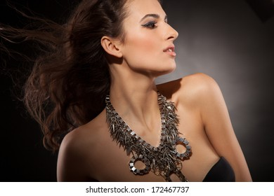 Beautiful Brunette Girl. Healthy Long Hair and Holiday Makeup. Jewelry. Perfect skin
