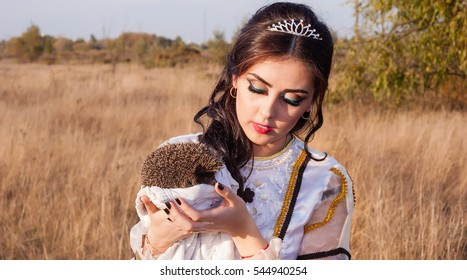 The beautiful brunette girl holds the real wild hedgehog. Girl and hedgehog.
