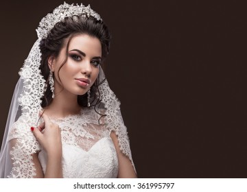 Beautiful brunette girl in the image of the Arab bride in a wedding dress and a crown on her head. Beauty face. Picture taken in the studio