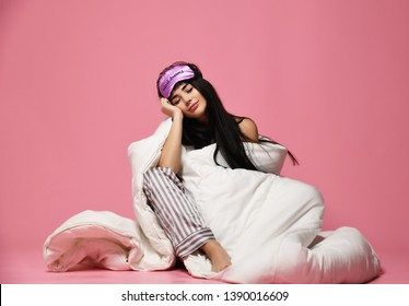 Beautiful brunette girl just woke up with soft pillow and blanket. Woman morning happy smiling want to sleep on pink background