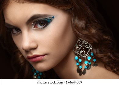 beautiful brunette girl with long curly hair and creative makeup