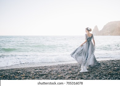 Beautiful brunette girl in long grey winding in the wind dress is made of tulle holds with one hand the dress looks profile on the seafront