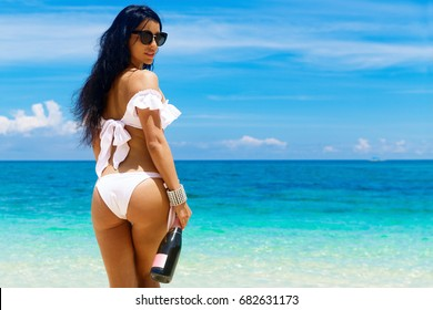 Beautiful brunette girl with long hair in bikini with bottle of champagne on a tropical beach with his back to the viewer. Summer vacation concept.