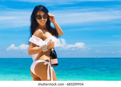 Beautiful brunette girl with long hair in bikini with bottle of champagne on a tropical beach. Summer vacation concept.