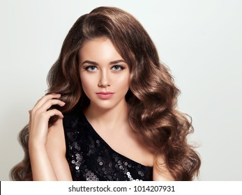 Beautiful brunette girl with long and volume shiny curly hair. Soft waves hairstyle.