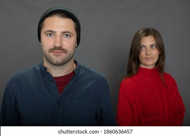 beautiful brunette girl looking at Handsome unshaven guy in knitted cap. Family couple on gray backdrop. marriage bonds, family relationship Problems, love secrets, cheating, Sexual disharmony concept