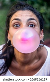 Beautiful brunette girl making a chewing gum balloon. Buenos Aires, Argentina. February 22, 2020