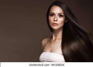 Beautiful brunette girl in move with a perfectly smooth hair, and classic make-up. Beauty face. Picture taken in the studio.