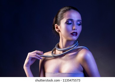 Beautiful brunette girl with naked shoulders and dark red lips make-up, wears a metal shower spiral hose wrapped around her neck. Concept and advertising low key photo illuminated in blue. Copy space