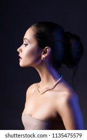 Beautiful brunette girl with naked shoulders and dark red lips make-up, wearing earrings and a pearl necklace, illuminated in blue. Conceptual low key photo. Copy space. Advertising design of jewelry.