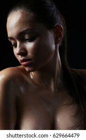 Beautiful brunette girl with a nude make-up and wet hair and skin. Beauty face. Photo taken in the studio on a black background.