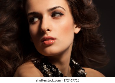 Beautiful Brunette Girl portrait. Healthy Long Hair and Holiday Makeup. Jewelry. Perfect skin