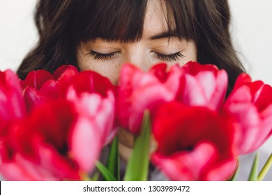 Beautiful brunette girl portrait with red tulips closeup on white background indoors, space for text. Stylish young woman  smelling tulips with closed eyes. Fresh aroma scent concept