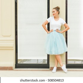 beautiful brunette girl posing in a blue skirt of tulle tutu and sneakers