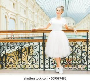 Beautiful brunette girl posing in a pink skirt of tulle tutu and sneakers in a beautiful old hall.