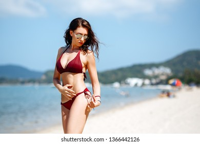 Beautiful brunette girl in a red bikini swimsuit and sunglasses posing on the beach on a Sunny day. Portrait of a woman on vacation against the sea.