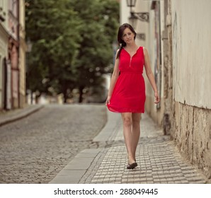 Beautiful brunette girl with red outfit in old town street