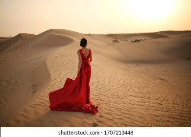 A beautiful brunette girl in a red silk dress with a train stands in the middle of the desert and looks at the sunset.