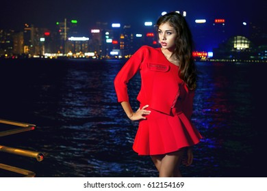 Beautiful brunette girl in a red suit stands on the waterfront on a background of a night city