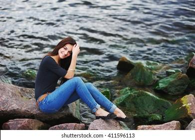 beautiful brunette girl sitting on the embankment near the river