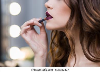 Beautiful brunette girl smears on bright Burgundy lip pencil, close-up, horizontal, cosmetics