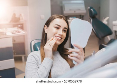 Beautiful brunette girl smiles in dentistry. Cost of a patient from a dentist. A beautiful model at the Dental Clinic. White well-groomed teeth after taking a doctor. Tooth whitening and tooth enamel