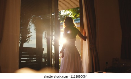 Beautiful brunette girl stands in the doorway in the early morning during sunrise with lens flare effects