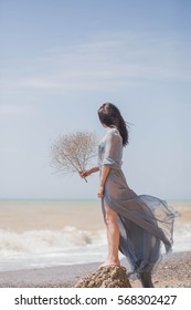 beautiful brunette girl stands on a rock by the sea in blue grey boudoir gown robe in the wind