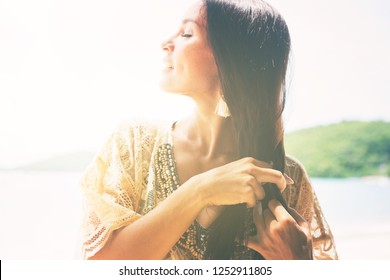 Beautiful brunette girl tie her hair into braid in lacy boho style dress. Beach walk. Copy space. Toned