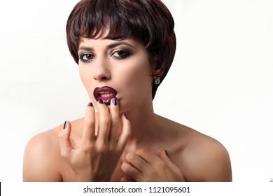 Beautiful brunette girl touching lips with makeup