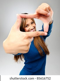 Beautiful brunette girl uses her fingers to frame her face, in studio isolated on grey