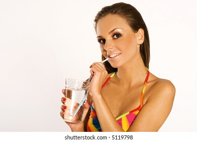 a beautiful brunette girl wearing colorful dress drinking on white background