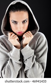 Beautiful brunette girl wearing hooded sweater and looking at camera. She's holding the hood like it's too cold.