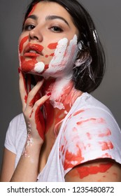 Beautiful brunette girl wearing a white t-shirt stained with paint touches her face and neck with her hand. Handprint of the palm and strokes of paint on her face. Conceptual, fashion design