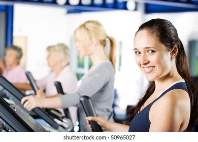 Beautiful brunette girl working out at the gym with a group of friends