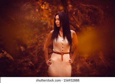 Beautiful brunette girl in yellow autumn brown dark mysterious forest look toward
