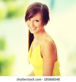 Beautiful brunette girl in yellow dress.